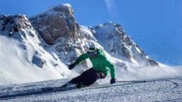 A skier carving down a piste in a private ski lesson in Courchevel